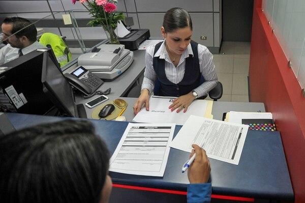 La mayoría de encuestados abrió sus cuentas bancarias de manera voluntaria. Un porcentaje menor lo hizo porque su patrono lo solicitó. Kimberly Núñez atendió a un cliente en el Banco de Costa Rica. | ARCHIVO
