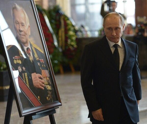 Vladimir Putin participó el viernes del funeral de Mijaíl Kaláshnikov, el inventor del mítico rifle de asalto AK-47. Aquí, pasa a un lado de un retrato del inventor. | AFP.