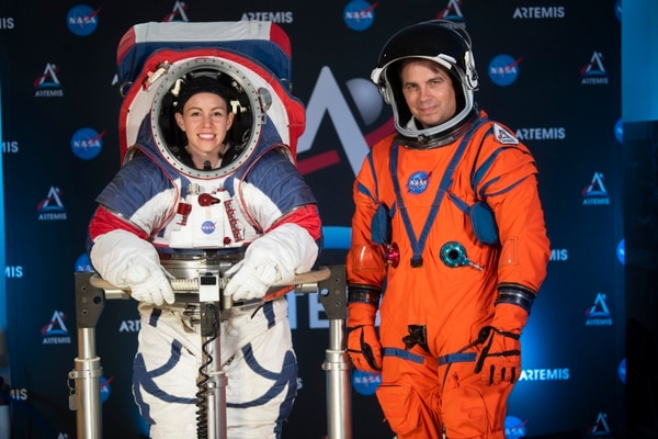 The two NASA spacesuit prototypes for lunar exploration, one for launch and re-entry aboard the agency's Orion spacecraft, known as the Orion Crew Survival Suit, is worn by Dustin Gohmert, right, and one for exploring the surface of the Moon's South Pole, known as the Exploration Extravehicular Mobility Unit (xEMU) is worn by Kristine Dans on Tuesday, Oct. 15, 2019, at NASA Headquarters in Washington. (AP Photo/Kevin Wolf)