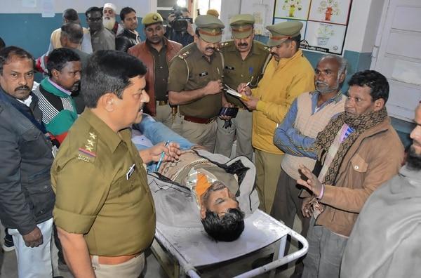 Policías custodiaban -el domingo 10 de febrero del 2019- el cuerpo de un hombre en el Hospital Civil de Saharanpur en Saharanpur, en el estado norteño de Uttar Pradesh. Fue una e las víctimas por ingestión de alcohol adulterado.