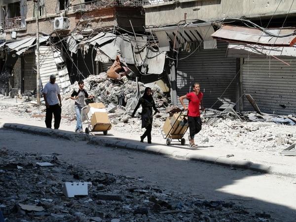 Residentes del campo de refugiados palestinos de Yarmuk, al sur de Damasco, salen a aprovisionarse de alimentos que les dan como ayuda.   AFP