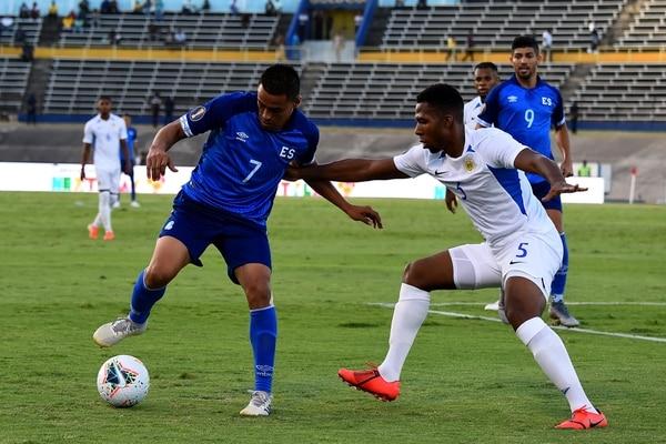 Darwin Ceren (azul) controla la pelota ante la marca de Jurich Carolina en el juego entre El Salvador y Curacao. Foto: CHANDAN KHANNA / AFP