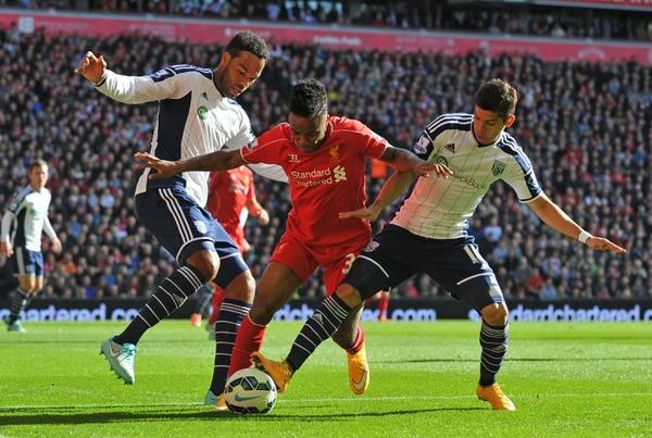 El delantero del Liverpool Raheem Sterling lucha por el balón ante la marca de Cristian Gamboa y Joleon Lescott (izq.) del West Bromwich.