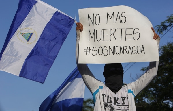 A masked demonstrator holding a Nicaraguan national flag and a sign with a message that reads in Spanish: