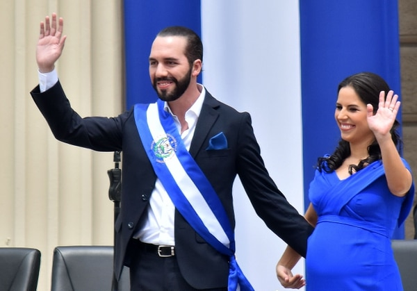 El nuevo presidente de El Salvador, Nayib Bukele, saluda junto con su esposa, Gabriela Rodríguez, durante la ceremonia de su investidura, en una plaza en el centro de San Salvador, el 1°. de junio del 2019. Foto: AFP