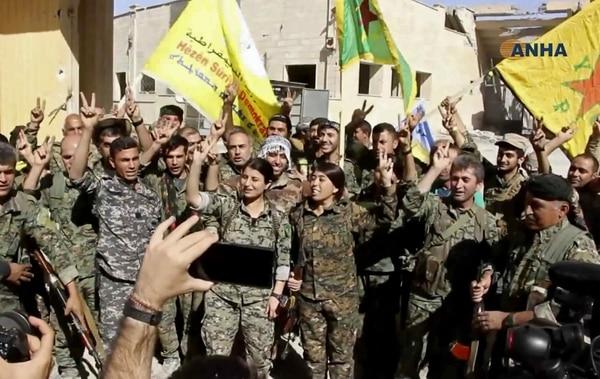 Esta captura de un video muestra a un grupo de combatientes de las Fuerzas Democráticas Sirias celebrando la toma de la ciudad de Raqa.