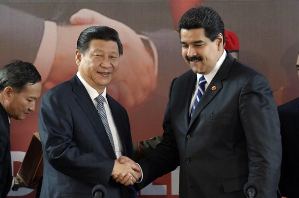 El presidente venezolano Nicolás Maduro (der.) saluda a su colega Xi Jinping durante la firma de acuerdos ayer en Caracas. | AFP