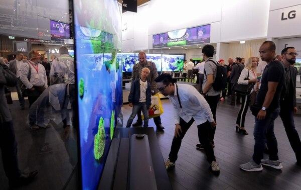 Los visitantes inspeccionan televisiones flatscreen en la cabina de LG en la Feria de Electrónicos en Berlín.